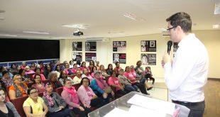 o médico Ricardo Oliveira da Fonseca fala ao microfone para um auditório lotado de mulheres