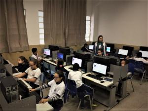 um laboratório de informática com uma turma de alunos sendo orientada por uma professora