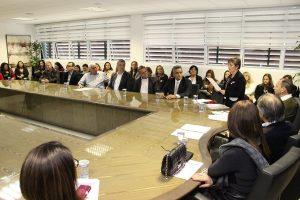 membros do conselho acompanham discursos em mesa de reuniões do gabinete do prefeito