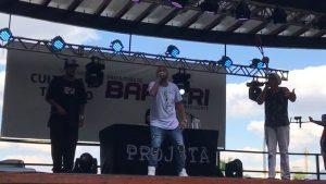 projota e dois rappers de apoio no palco e um DJ ao fundo, logo atrás de projota
