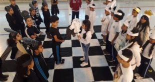 alunos posicionados em cima de um tabuleiro gigante de xadrez, como se fossem peças