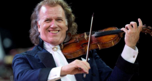André Rieu de terno sorrindo e tocando violino