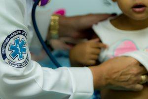 uma criança cujo rosto não é mostrado sendo examinada por um(a) médico(a) em barueri