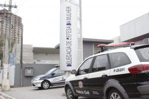 fachada da delegacia de defesa da mulher de barueri, com uma viatura da polícia civil e outra da guarda civil estacionadas em frente