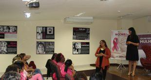 mulheres de rosa acompanham palestrantes, que estão no palco