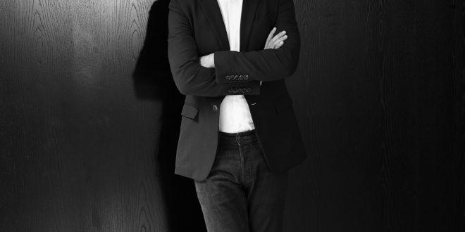 foto em preto e branco de carlos jereissati filho de terno, com os braços cruzados, apoiado em uma parede e sorrindo para a câmera