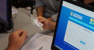 um servidor recebendo documentos de um munícipe com um computator entre eles; somente as mãos deles são vistas