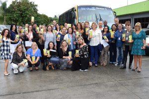 agentes do fundo social posam com cofrinhos em maos diante de ônibus que as levará à AACD