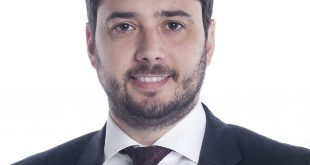 Francisco Finocchiaro de terno sorrindo para a câmera ante um fundo branco