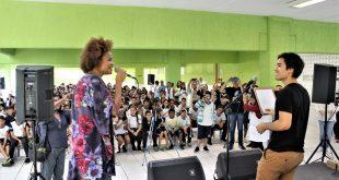 luciana melo se apresentando no palco da Emef Sidney Santucci com um músico, com o público acompanhando atrás