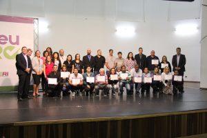participantes do programa posam no palco com certificados em mãos