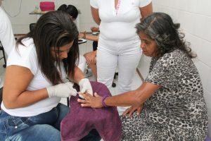 uma manicure trabalhando a mão de uma senhora