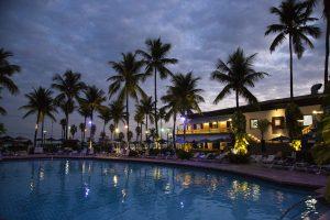 uma piscina no Casa Grande Hotel rodeada de palmeiras e pelo próprio hotel
