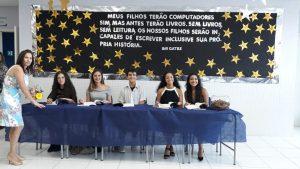 alunas escritoras em mesa para autografarem livros