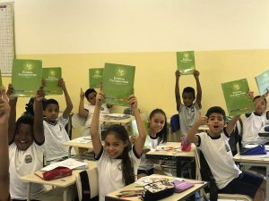 alunos posam com kits do uniforme escolar em mãos