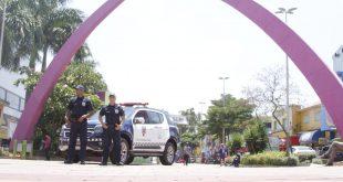 dois guardas civis de barueri em frente a uma viatura e embaixo de um grande arco roxo