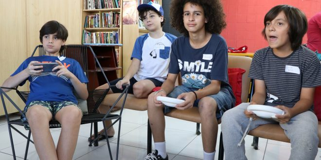 garotos jogando videogame na biblioférias