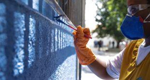 pessoa pintando de azul o muro de uma escola