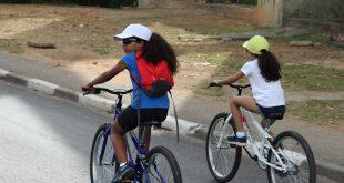 duas meninas andando de bicicleta com bonés e óculos escuros