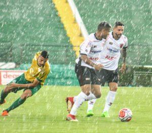 dois jogadores do oeste disputam uma bolsa com jogador do Guarani debaixo de forte chuva